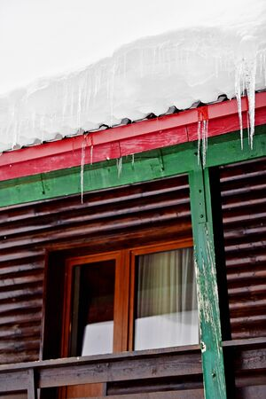 chalet: Winter detail with melting icicles on a wooden chalet