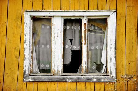home destruction: Facade of an abandoned wooden house with broken windows