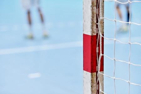 balonmano: Detalle el tiro con poste de la portería de balonmano y los jugadores en el fondo