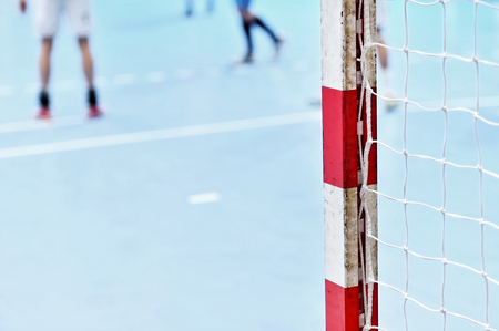 goalpost: Detail shot with handball goalpost and players in the background Stock Photo