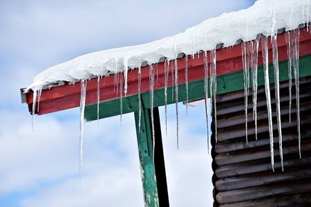chalet: Winter detail with melting icicles on the roof of wooden chalet