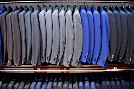 hangers: Elegant blue and gray suits on hangers are seen in a suit store Stock Photo