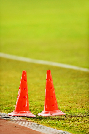 sideline: Orange soccer marker cones for training are seen on the sideline of a soccer field