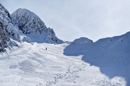 fagaras: Mountaineer climbing with crampons on alpine valley in Fagaras Mountains in Romania