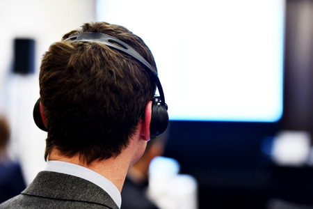 translation: Unrecognizable people using in ear headphones for translation during event Stock Photo