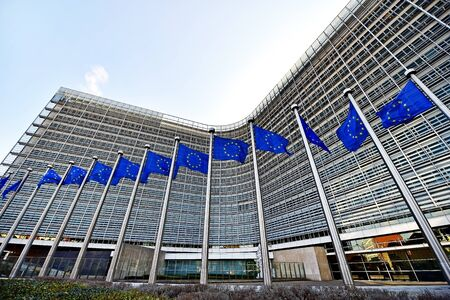 BRUSSELS, BELGIUM - MARCH 16: EU flags blown by wind in front of the European Commission Headquarters, also know as the Berlaymont building, on March 16, 2016 in Brussels. Editoriali