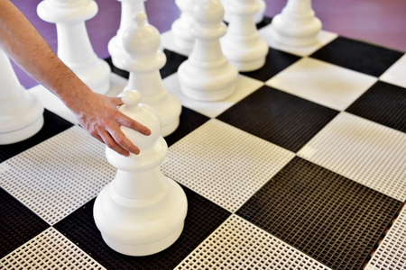 chellange: Hand moving a pawn on a giant chess game