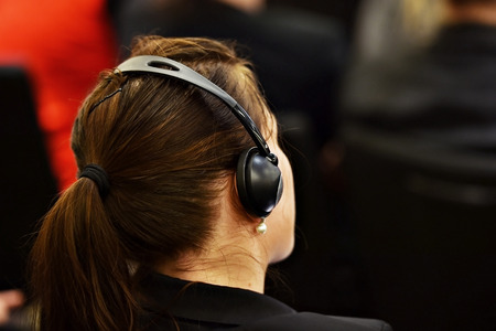 Unrecognizable woman using headphones for translation during event Stock Photo