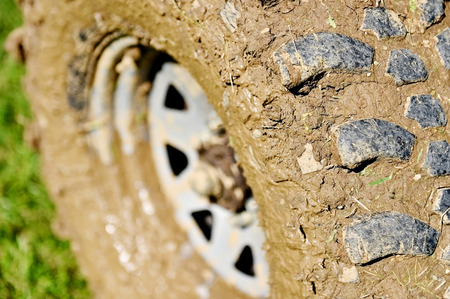 off road: Big vehicle off road wheel and tire full of mud on green grass