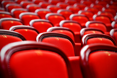 color design: Rows of empty red velvet seats inside a theater