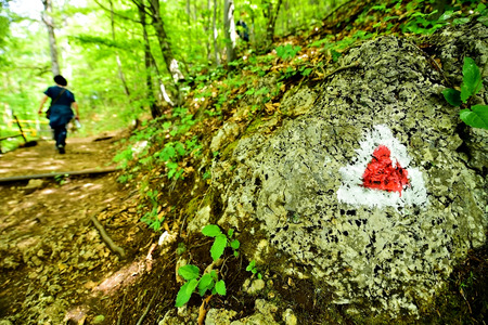 resplandor: Hiking red triangle paint marking on a rock with hiker on the trail Foto de archivo
