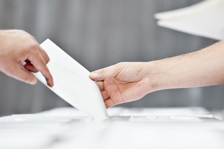 secrecy of voting: Hand of a person casting a vote into the ballot box during elections