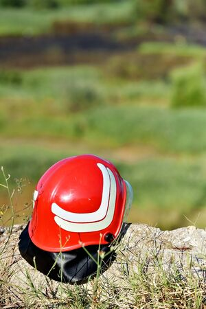 Firefighter helmet on the ground with extinguished fire in background