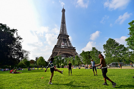 champ: PARIS, FRANCE - JUNE 8: People playing soccer in Champ de Mars park near the Eiffel Tower during the UEFA 2016 European Championship on June 8, 2016 in Paris.