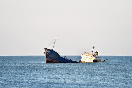 海岸線の近くの海に放棄された産業の難破船