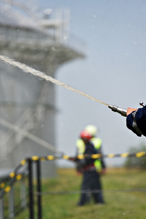 extinguishing: Firefighter holding high pressure water hose extinguishing a fire started near a petrol storage tank Stock Photo