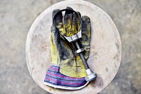 Dirty workers glove holding a oil filter key on a wooden plank in a workshop