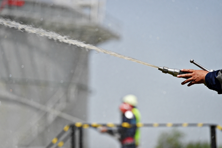 Firefighter holding high pressure water hose extinguishing a fire started near a petrol storage tank Stock Photo