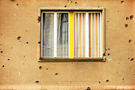 shrapnel: Traces of bullets on a building facade destroyed by war