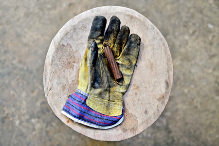 Dirty workers glove holding a rusty spring on a wooden plank in a workshop