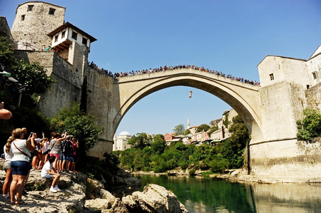 neretva: MOSTAR, BOSNIA AND HERZEGOVINA - AUGUST 29: Tourists watch a high diver jumping from the old bridge of Mostar into Neretva river on August 29, 2015 in Mostar.