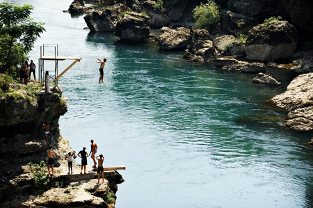 neretva: MOSTAR, BOSNIA AND HERZEGOVINA - AUGUST 29: People doing high diving into the Neretva river on August 29, 2015 in Mostar.