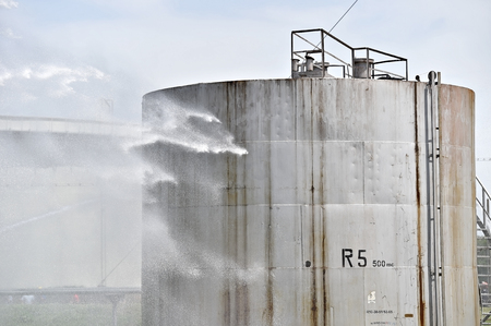 extinguish: Firefighter water jet extinguish the fire started near a petrol storage tank