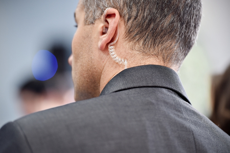 Detail with a bodyguard wearing in ear headset Stock Photo