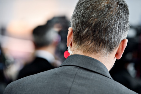 under surveillance: Detail with a bodyguard wearing in ear headset Stock Photo