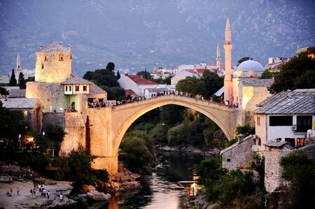 bosnia hercegovina: Tourists on the the old bridge of Mostar, known as Stari Most, at sunset