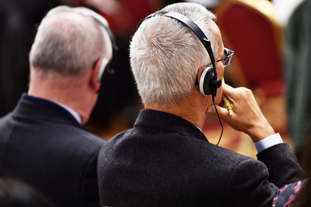 Onherkenbaar persoon met behulp van in-ear hoofdtelefoons voor de vertaling tijdens evenement Stockfoto