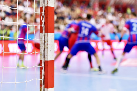 Handball match scene with goalpost and players in the background Stok Fotoğraf