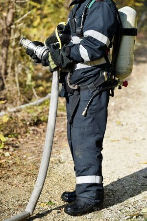 Firefighter holding high pressure water hose extinguishing a fire