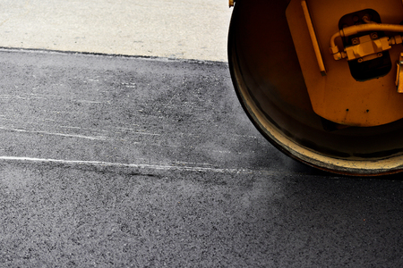 steam roller: Asphalt paving with a steel wheel roller. Steam coming out from asphalt.