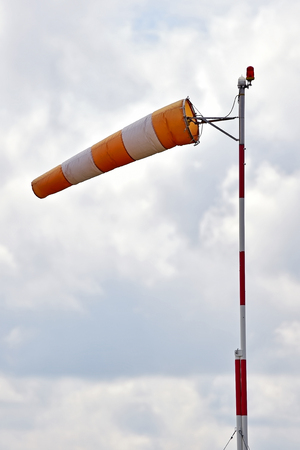 Windsock blown by the wind with overcast sky on background Stock Photo