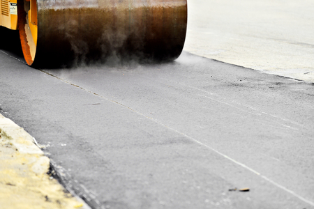 asphalting: Asphalt paving with a steel wheel roller. Steam coming out from asphalt.