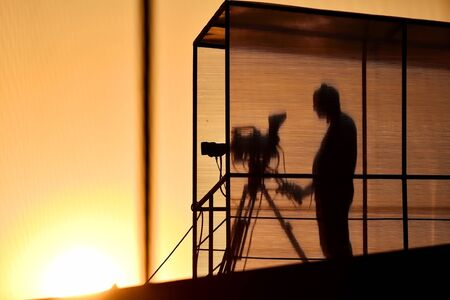 newscast: Cameramans silhouette broadcasting live from a stadium