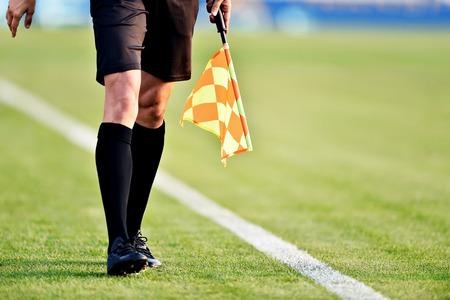 Árbitro asistente moviéndose a lo largo de la línea lateral durante un partido de fútbol