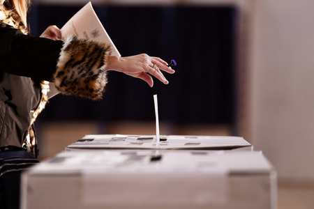 Hand with a stamp casting a vote into the ballot box during elections Stock Photo