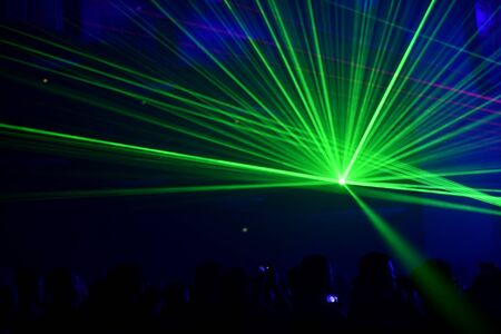 Unrecognizable people watching a beautiful laser show with multicolored lights Stock Photo