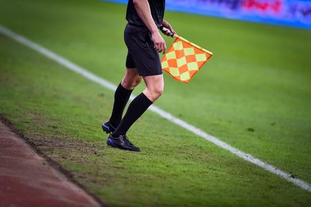 Rbitro asistente moviéndose a lo largo de la línea lateral durante un partido de fútbol Foto de archivo - 73538524