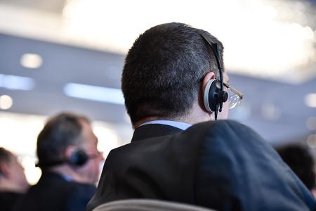 Unrecognizable business people using headphones for translation during event Reklamní fotografie