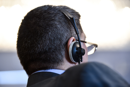 Unrecognizable business people using headphones for translation during event Stock Photo