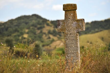 Ancient stone orthodox cross deserted on a plain