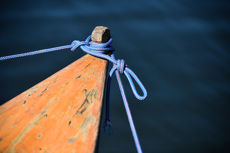roped: Wooden canoe roped up to the shore Stock Photo