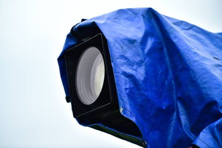 Television news camera on a tripod protected by a blue rain cover