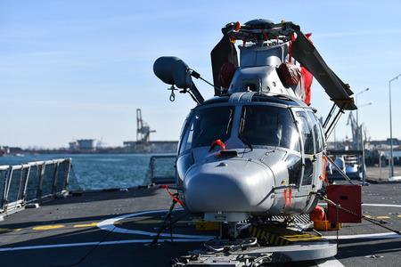 Helicopter parked on a platform of a war frigate