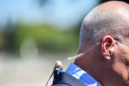 Detail with in ear headphone during a live broadcast by a reporter