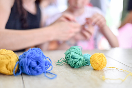 Hands of an adult and hands of a child knitting together