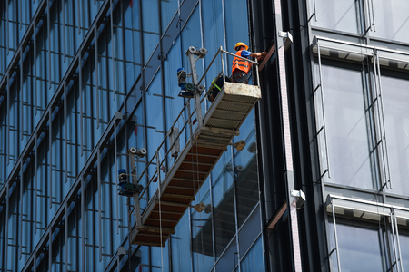 Construction workers on a suspended platform on a skyscraper glass facade